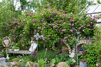 Enchanting seat, Rosa 'Himmelsauge' and two stone built arches