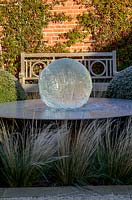 Aqualens water feature designed by Allison Armour with large clipped balls of Buxus sempervirens, Stipa tenuissima grass and Traschelospermum jasminoides on brick wall, on a frosty morning.