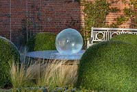 Aqualens water feature designed by Allison Armour with large clipped balls of Buxus sempervirens and Stipa tenuissima grass