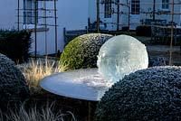 Aqualens water feature designed by Allison Armour with large clipped balls of Buxus sempervirens and Stipa tenuissima grass.