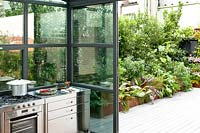 Outdoor kitchen with view to planted corten containers on the terrace