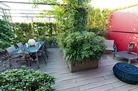 Overview of decked roof garden with dining area under pergola, a red partition and planters with shrubs for screening