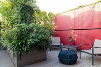 Roof garden with red partition with seating in front, decked surface with same material used for large planter of shrubs that divides the space up