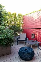 A red partition with seating in front, decked surface with plant screens in troughs