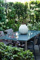 A dining corner on a terrace, plant screening from Hydrangea 'Limelight', in the foreground purple-leaved Loropetalum 'Black Pearl'