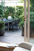View from the inside through open glass doors to decked dining area screed by shrubs