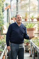 Nurseryman holding a potted Agave in a greenhouse