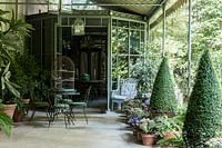 Two shady verandas connect the outdoor area dominated with pots of purple flowers preferred by Pierre Berge