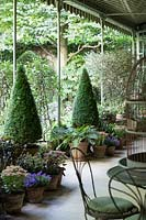 Shady veranda with pots flowers in purple and purple tones those preferred by Pierre Berge