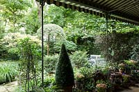 Shady veranda that has mixed pots in groups with a view to the garden planted with green shrubs