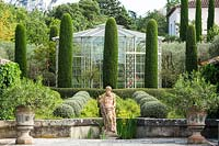 Mixed topiary on the terrace with figurative sculpture. The garden focuses on perfumed evergreens - pitosfori, olive trees, oleanders and lonicera nitida.