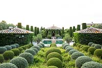 Mixed topiary spheres beside the swimming pool. The garden focuses on perfumed evergreens
