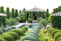 Mixed topiary beside the swimming pool with figurative sculpture.  The garden focuses on perfumed evergreens