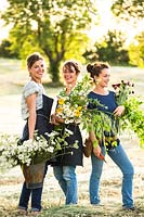 Three nurserywomen holding bunches of cut flowers out in field