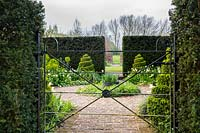 Garden metal gate through Taxus 'Yew' hedge to formal 'White garden' with Tulips and spiral Buxus 'box' topiary.
