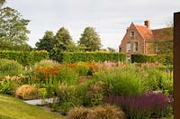 Large perennial beds in a country garden, hedge and house beyond