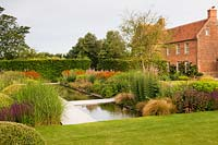 Modern formal pond, between flower beds in a country garden