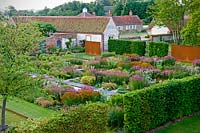 Overview of modern formal country garden, flower beds in blocks surrounded by hedges with view of buildings beyond