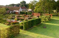 Overview of modern formal country garden, neat lawns, hedges and flower beds