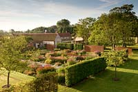 Overview of modern formal country garden with lawn, trees hedges and flower beds