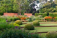 Modern formal country garden: lawn divided by rusted metal edging with topiary domes, deep flower beds, metal walls and trees