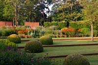 Modern formal country garden: lawn divided with rusted metal edging, topiary domes and deep flower beds, metal walls, hedging and trees beyond