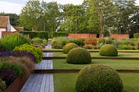 Modern formal country garden, view along decked path next to lawn divided by rusted metal edging, topiary domes and flower beds with trees beyond
