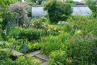 View of walled garden with wide range of herbaceous perennials including irises, geraniums, peonies, alchemilla, hemerocallis and delphiniums.