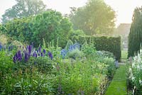 View of walled garden with wide range of herbaceous perennials including Chamaenerion angustifolium 'Album', delphiniums and hollyhocks.