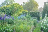 View towards house across walled garden with grass path and wide range of herbaceous perennials including Chamaenerion angustifolium 'Album', delphiniums and hollyhocks.
