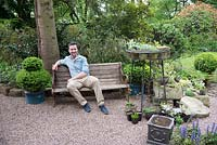 Man sitting on wooden bench in shade in a gravel area with pots of plants