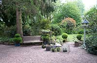 View of a shaded garden with gravel area, seating, pots, topiary with lawn trees and shrubs