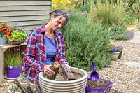 Woman adding logs to the base of a large plastic planter
