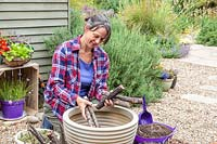 Woman adding cut branches to the base of a large plastic planter
