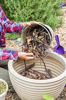 Woman adding a bucket of small twigs to large plastic planter