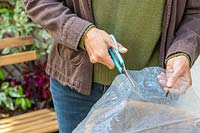 Woman using scissors to cut clear plastic to use as a liner for a hanging basket