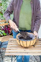 Woman filling lined hanging basket with compost