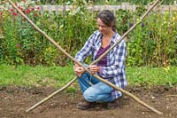 Woman using garden string to tie together two hazel poles