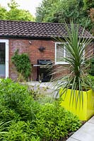 Small Modern Garden  with outdoor cooker and Cordyline in yellow pot