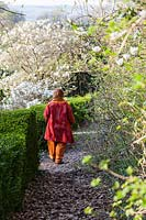 Anne Wareham on the path of the Magnolia Walk. Veddw House Garden, Monmouthshire, Wales, UK.