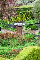 Central birdbath in centre of pathway, surrounded by flowering borders. Veddw House Garden, Monmouthshire, Wales, UK.