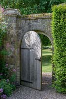 Wooden door in wall leading to the garden, Centranthus on the left in June.