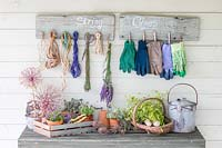 Rustic boards with wooden pegs attached for storing string and gloves