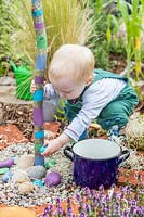 Young toddler playing with stones in sensory garden