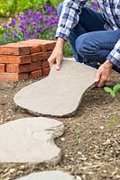 Woman laying paving slabs directly on soil to make a stepping stone pathway