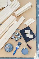 Materials and tools required to assemble a kit form raised planter on casters