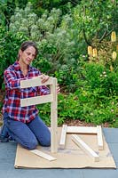 Woman inserting side panels for a raised planter being built from a kit