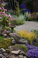 View over rocks and birdbath to flowering borders in small paved courtyard garden.