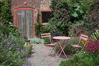 Pink metal table and chairs by brick potting shed in small paved courtyard.