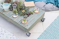 Finished pallet table with succulents on patio, with rugs and beanbag seating.
